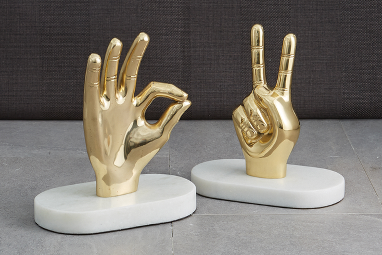 The Peace accessory is a hand sculpture forming a peace sign. Made from gold-finished aluminum and white marble, it adds a splash of metallic color to any space.
