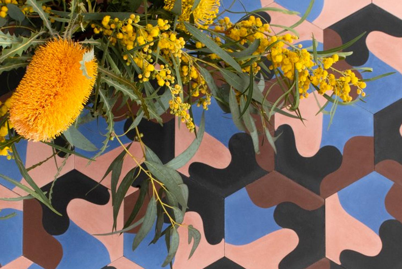 The eight-inch diameter hexagonally-shaped cement tiles sport an organic undulating wave or petal motif.