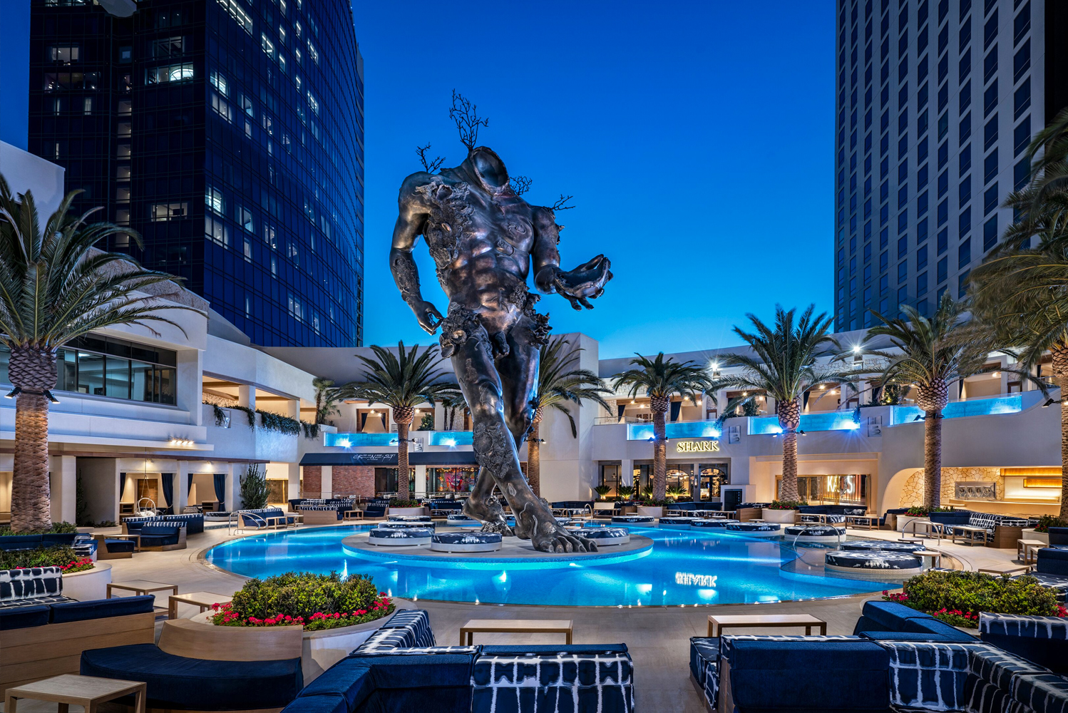 "The focal point of the dayclub is a towering 65-foot bronze sculpture by artist Damien Hirst entitled ""Demon with Bowl"" (2014) which rises from the center of one of the two main pools."