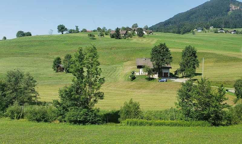 Austrian Lake District scenery includes rolling green hills in the shadow of higher mountain peaks.