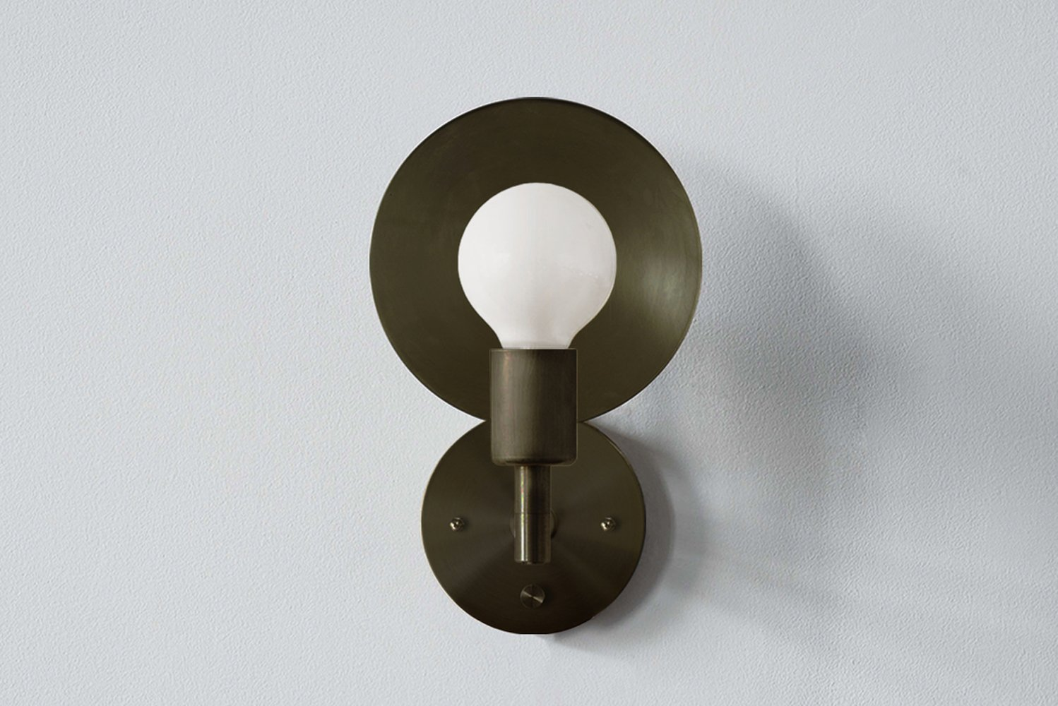 The sconce has a reflective spun brass disc rotating 320 degrees, so that the sconce can act as both a reflector and deflector of light.