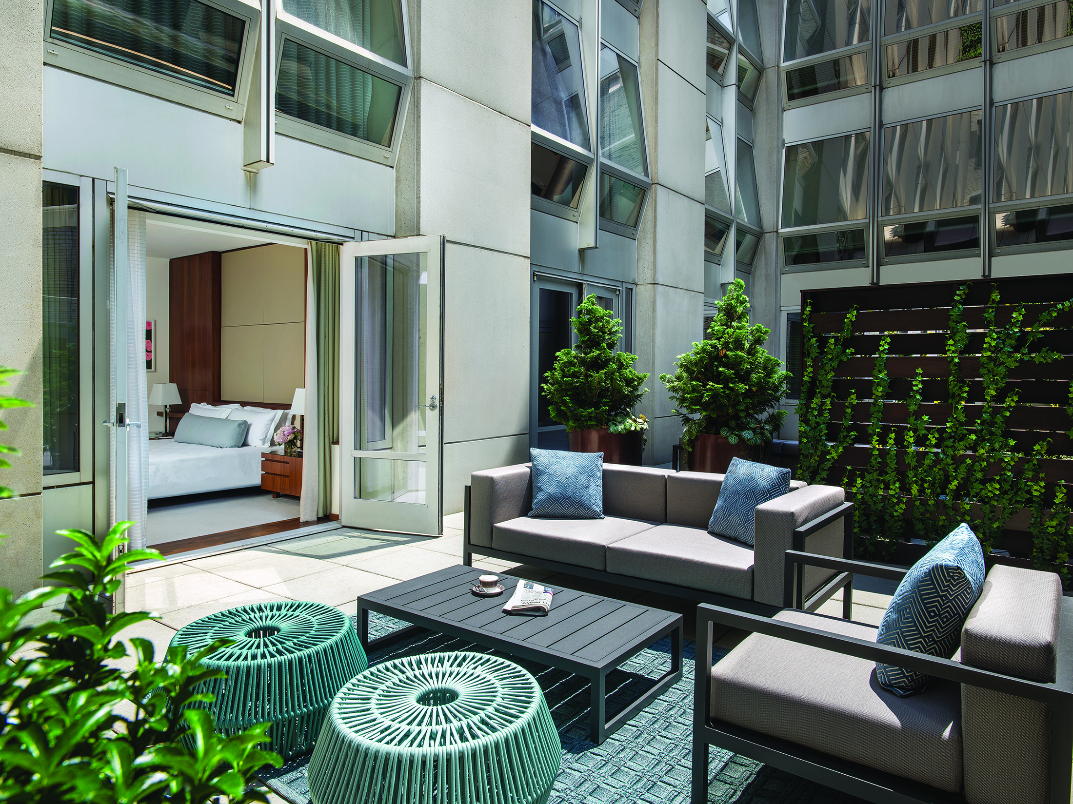 The fifth-floor terraces are walled-in private enclaves with teal furnishings.