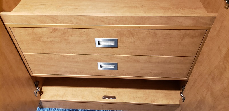 Two very wide storage drawers, as well as a shelf below are located within the closet.