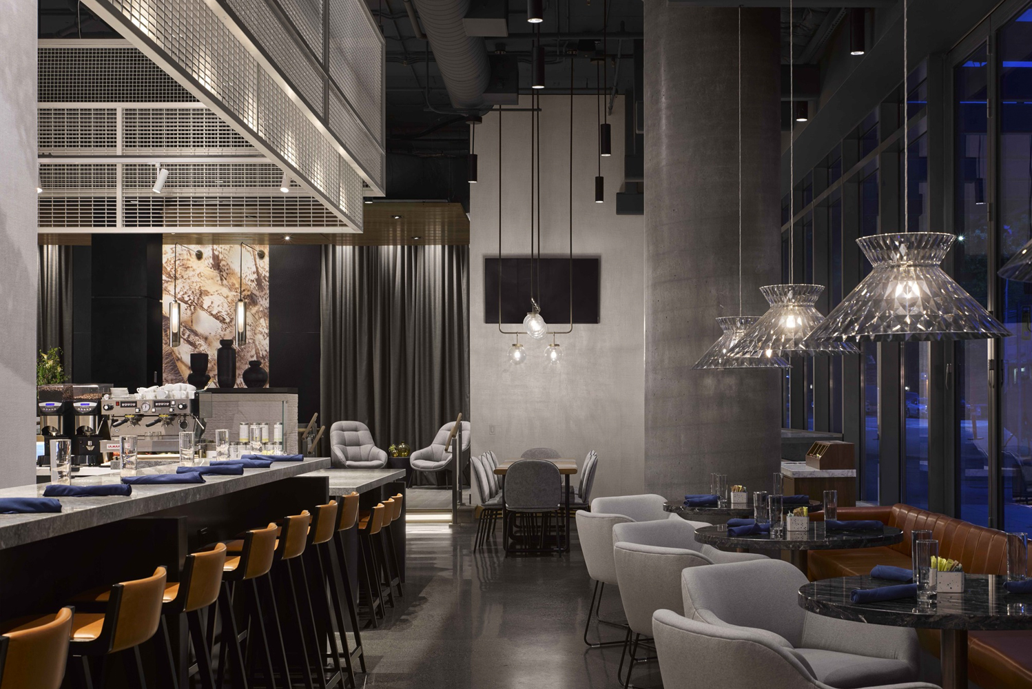A dramatic ceiling feature anchors the bar within the club lounge. Also available are seating in cognac and blush hues.