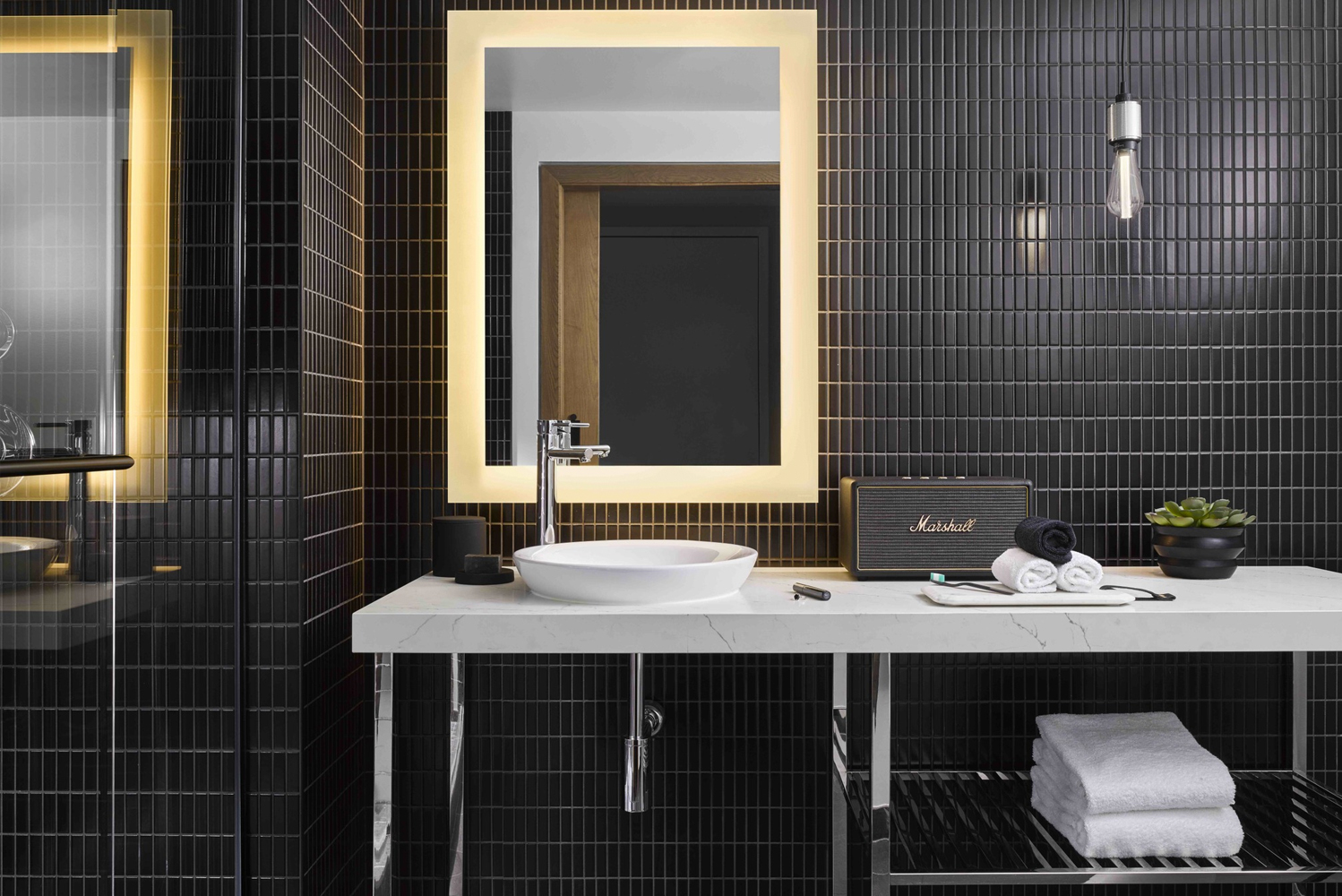 The dark bathrooms are reminiscent of backstage dressing rooms with microphone lights, robes, metal accents and black linear tiles.