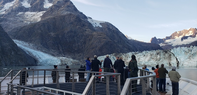 Guests on National Geographic Venture check out a glacier from the ship's bow. Photo by Susan J. Young.