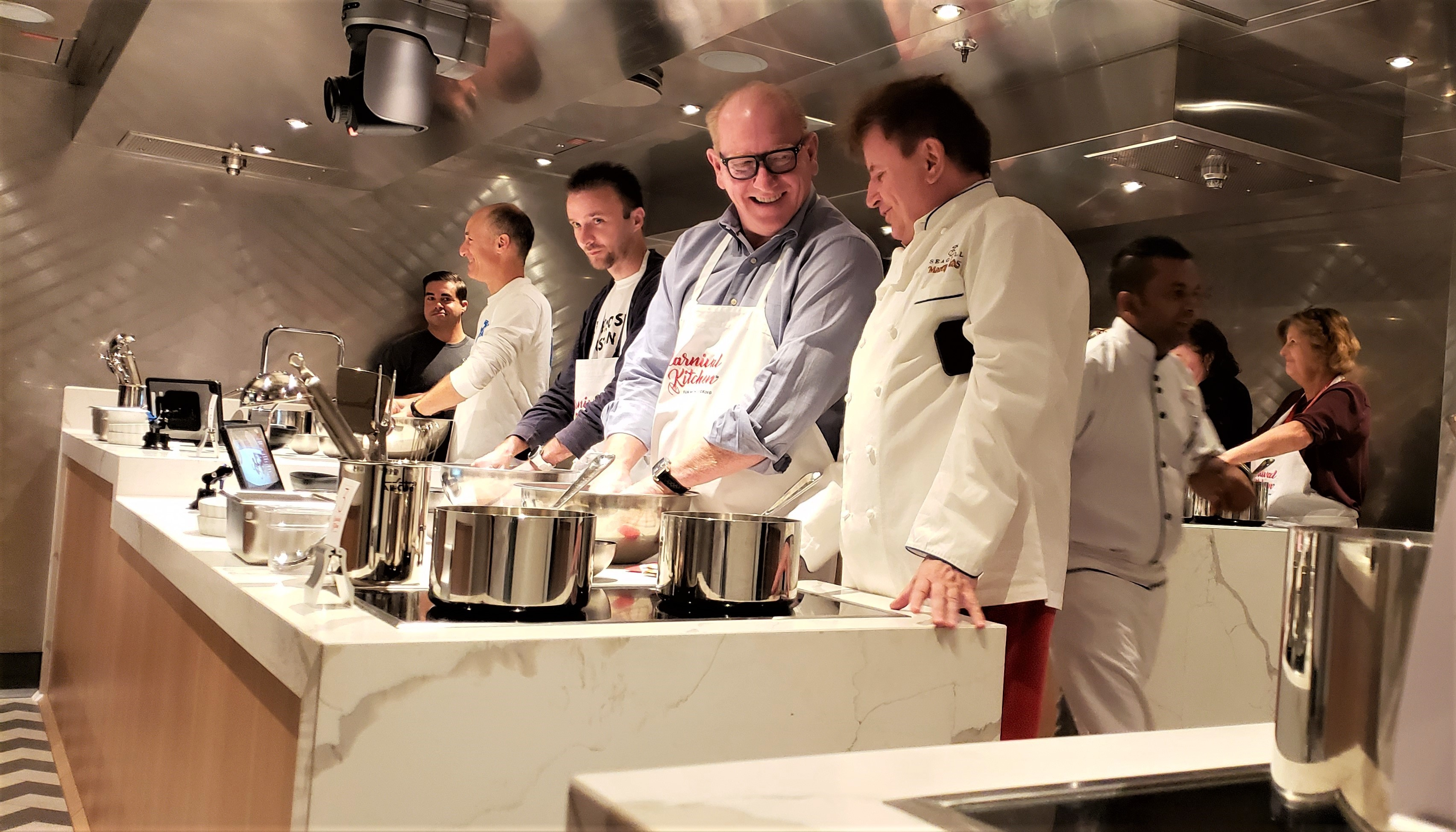 Guests try out the cook stations on the new Carnival Kitchen with Chef Rudi Sodamin (at right). Photo by Susan J. Young