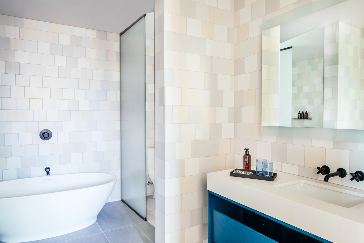 Bathrooms have glass walk-in showers, with select rooms offering freestanding soaking tubs.