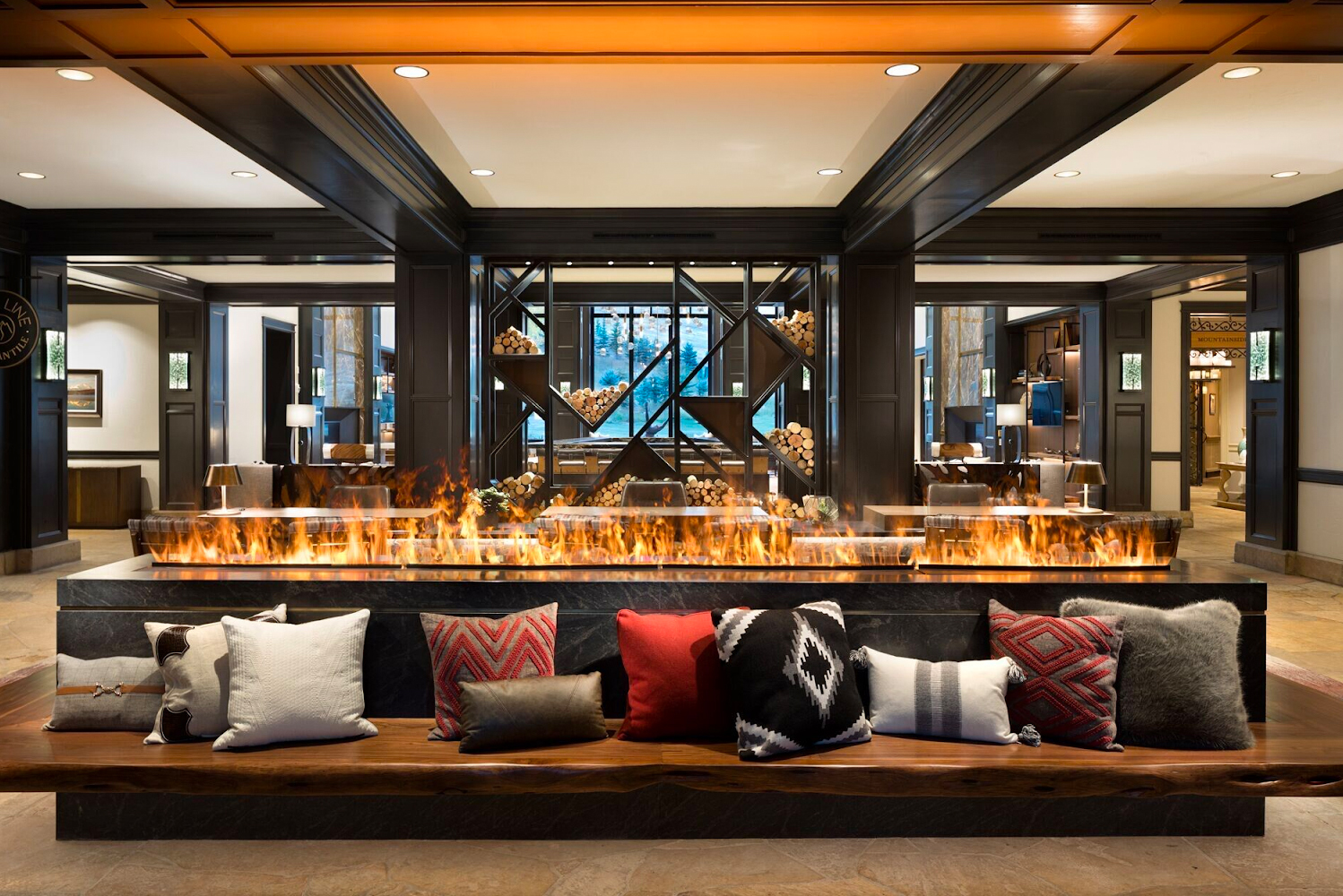 Upon entering the new lobby, guests are now met with a central, cantilevered live-edge wood bench that frames a honed-back granite fireplace.