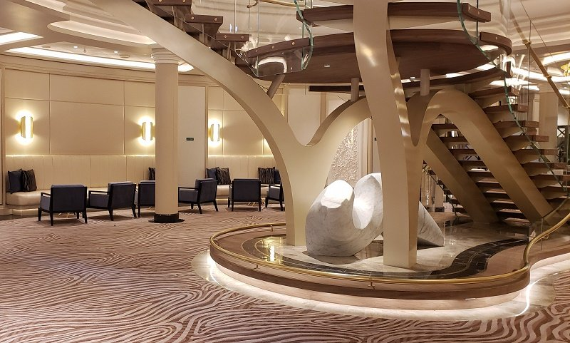 Spacious public spaces are a hallmark of Seven Seas Splendor, as in this area on Deck 4 with guest seating near the elevators and grand staircase. Photo by Susan J. Young