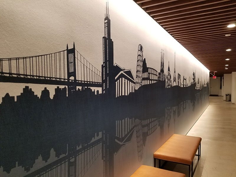 A mural of New York City greets arriving guests