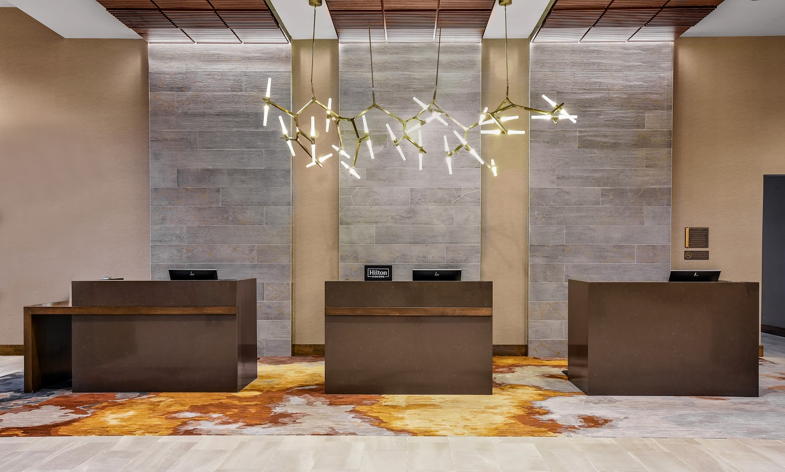 The hotel's opening reception area has a gray accent wall with gold crackle and a lighting fixture that resembles modern tree branches.