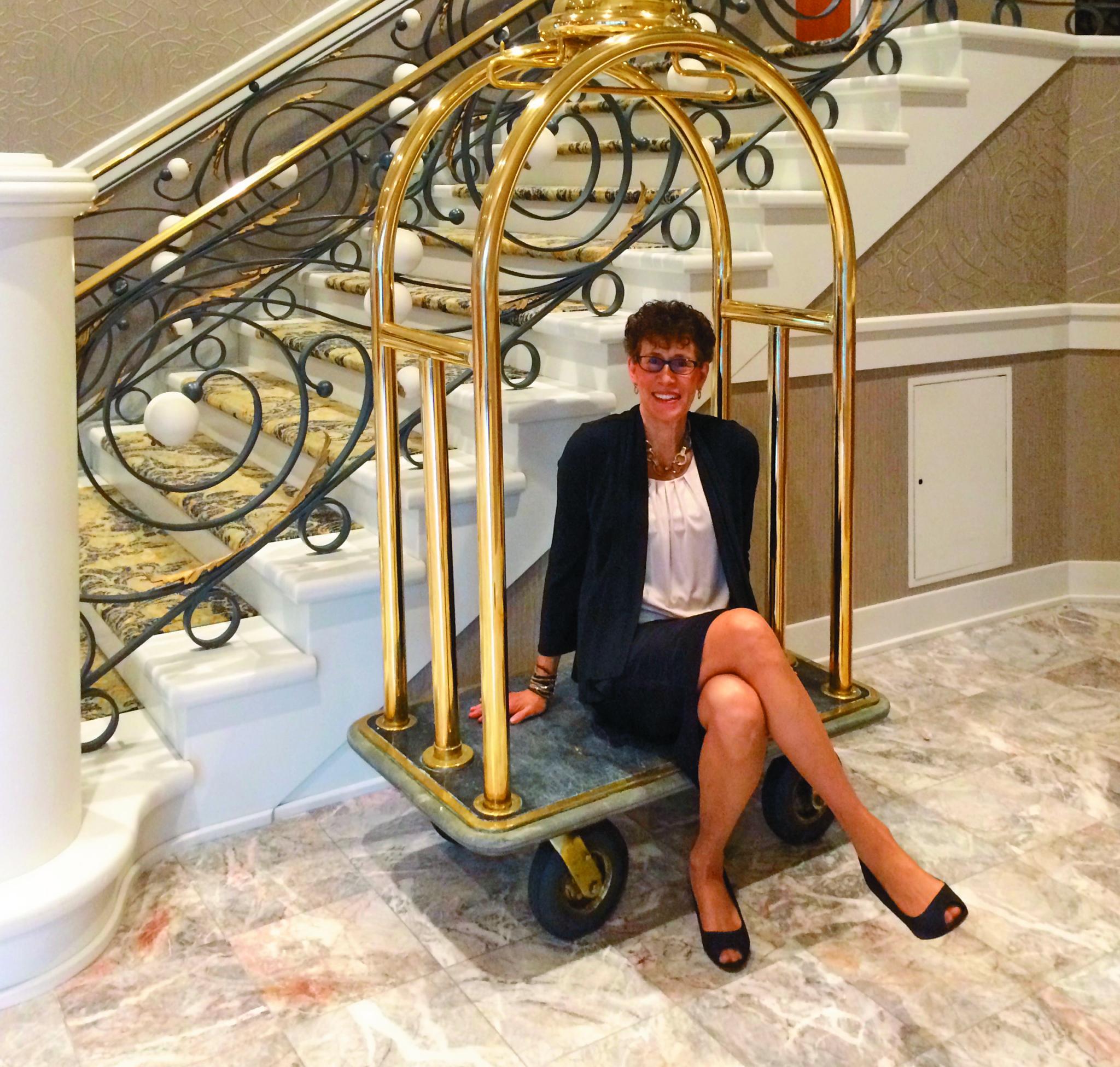 Karen Morris sitting on a hotel luggage cart