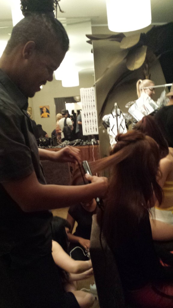 Chuck Amos straightening the model's hair