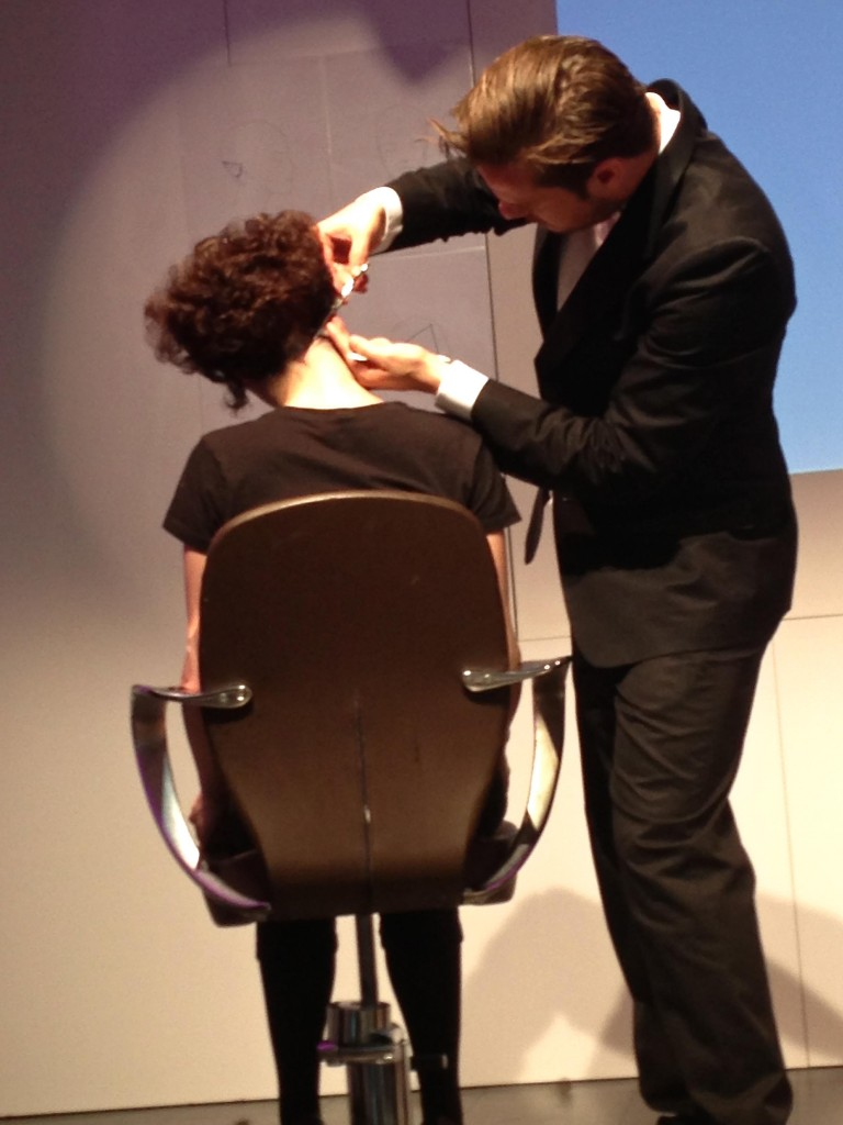 One of the team members of Mazella & Palmer demonstrating a new haircut technique for the artists on the stage.