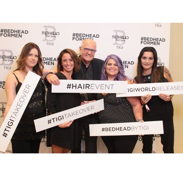A group from Stephen Szabo Salon (@stephenszabossalon) posed in front of the step and repeat.