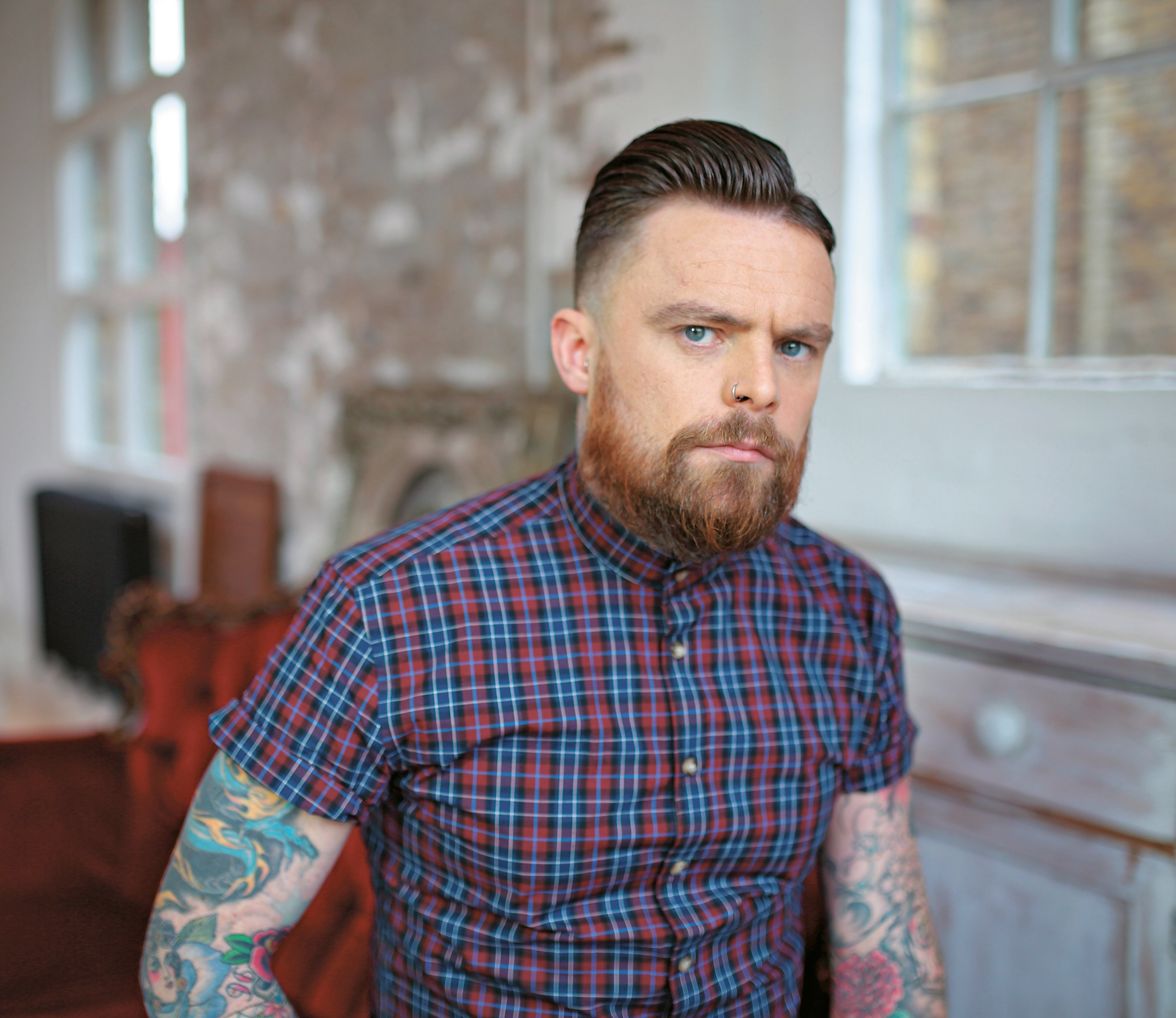 """Stylist Jon Bourne transformed the traditional """"hipster"""" look with a debonair pompadour and a  short-trimmed beard."""
