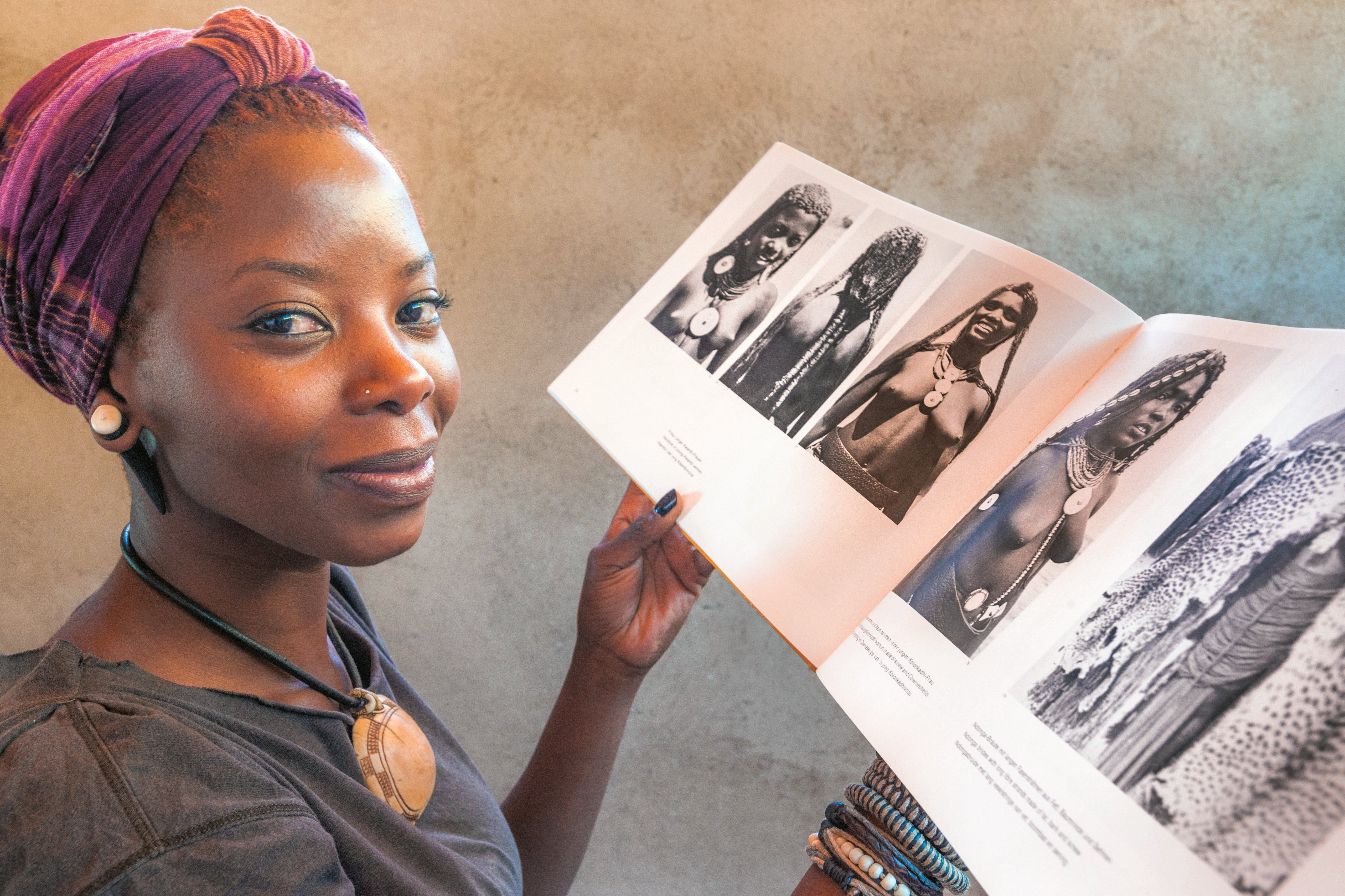 A Namibian woman with historical photos of tribal women from Ovamboland, Namibia.