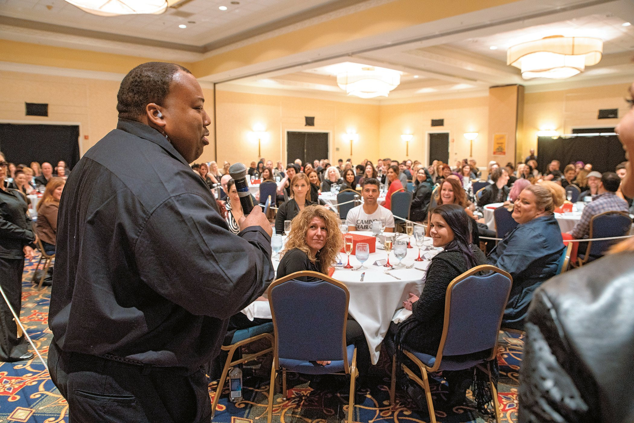 A visually inspired waiter shares his personal story with the attendees during the Dining in the Dark luncheon.