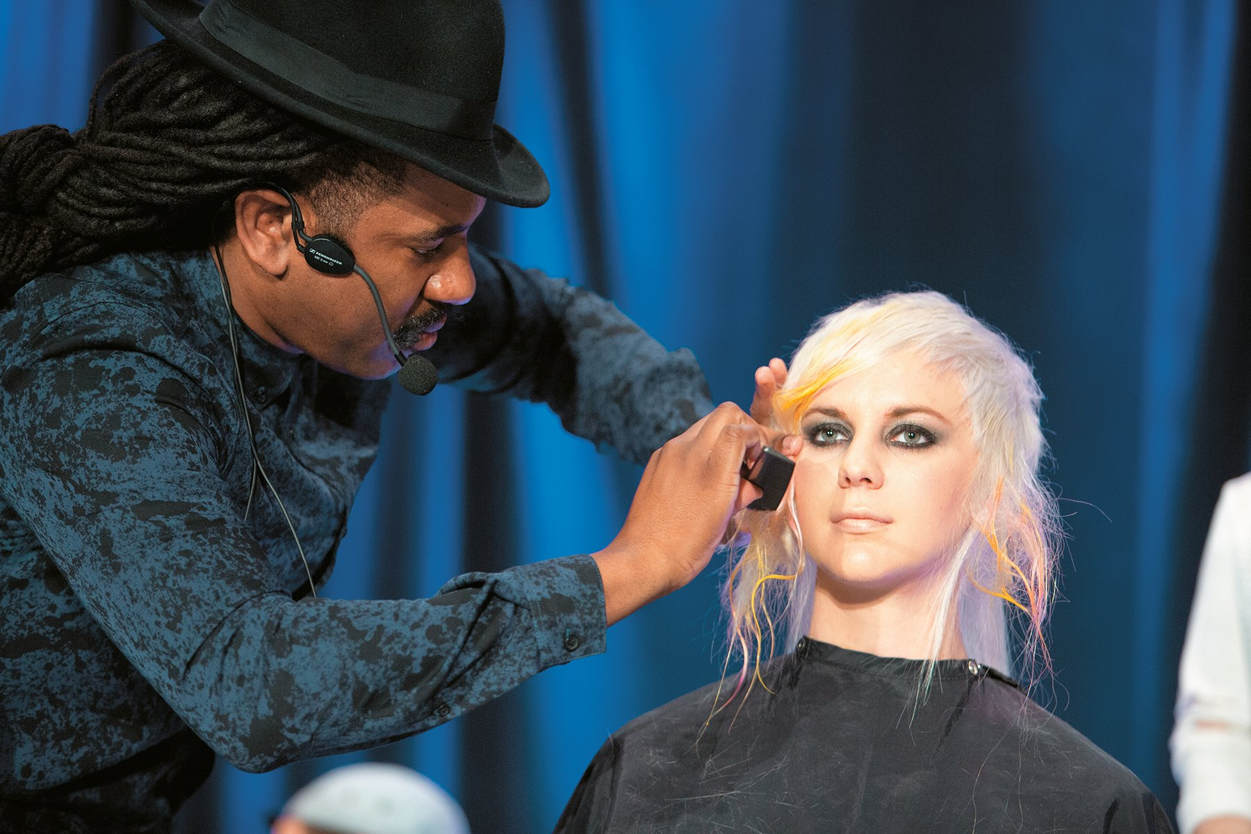 DJ Riggs cutting hair on the Hairbrained Teach In Stage.