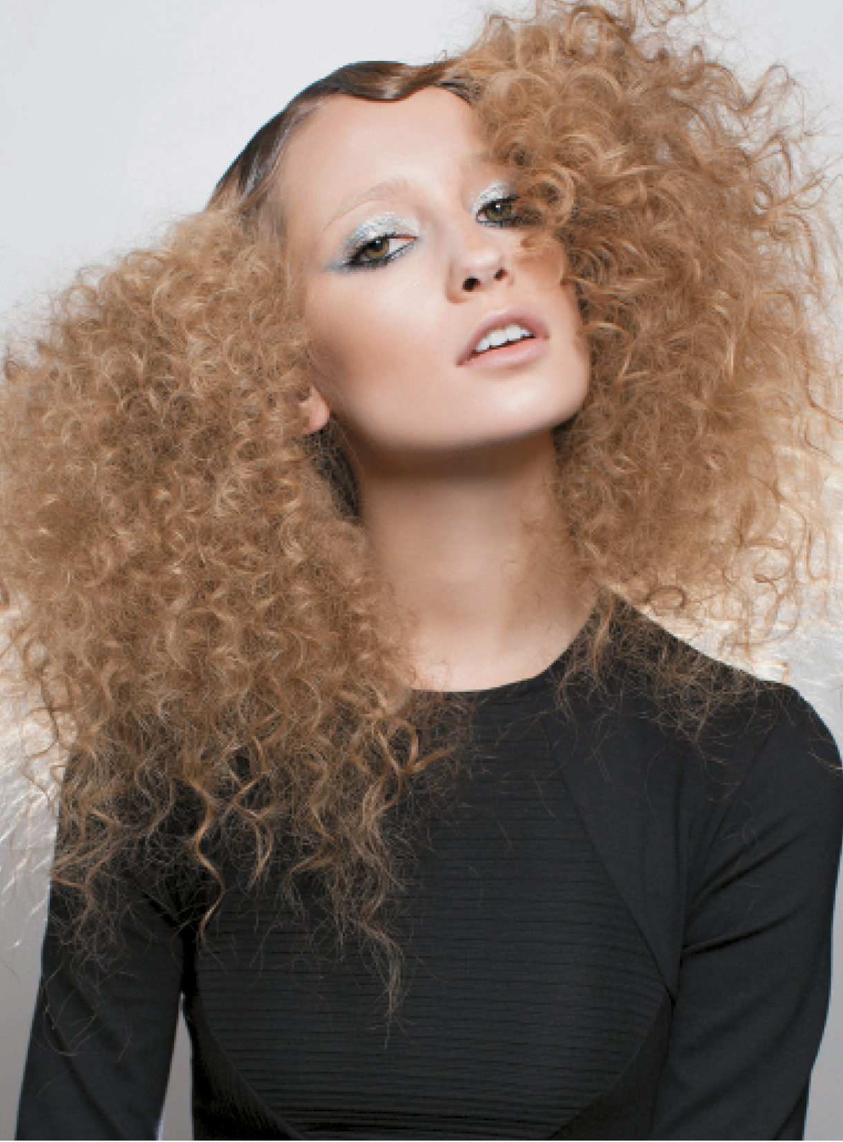 For this blonde, curly style, Buccio created finger waves at the area closest to the scalp, relying on Osis Gelflex for a sleek, wet effect. He separated every wave and curl, and brushed out some areas. To create luscious volume and texture, Buccio maintained a straight line at the top of the head and used Osis Elastic hairspray for moveable hold.
