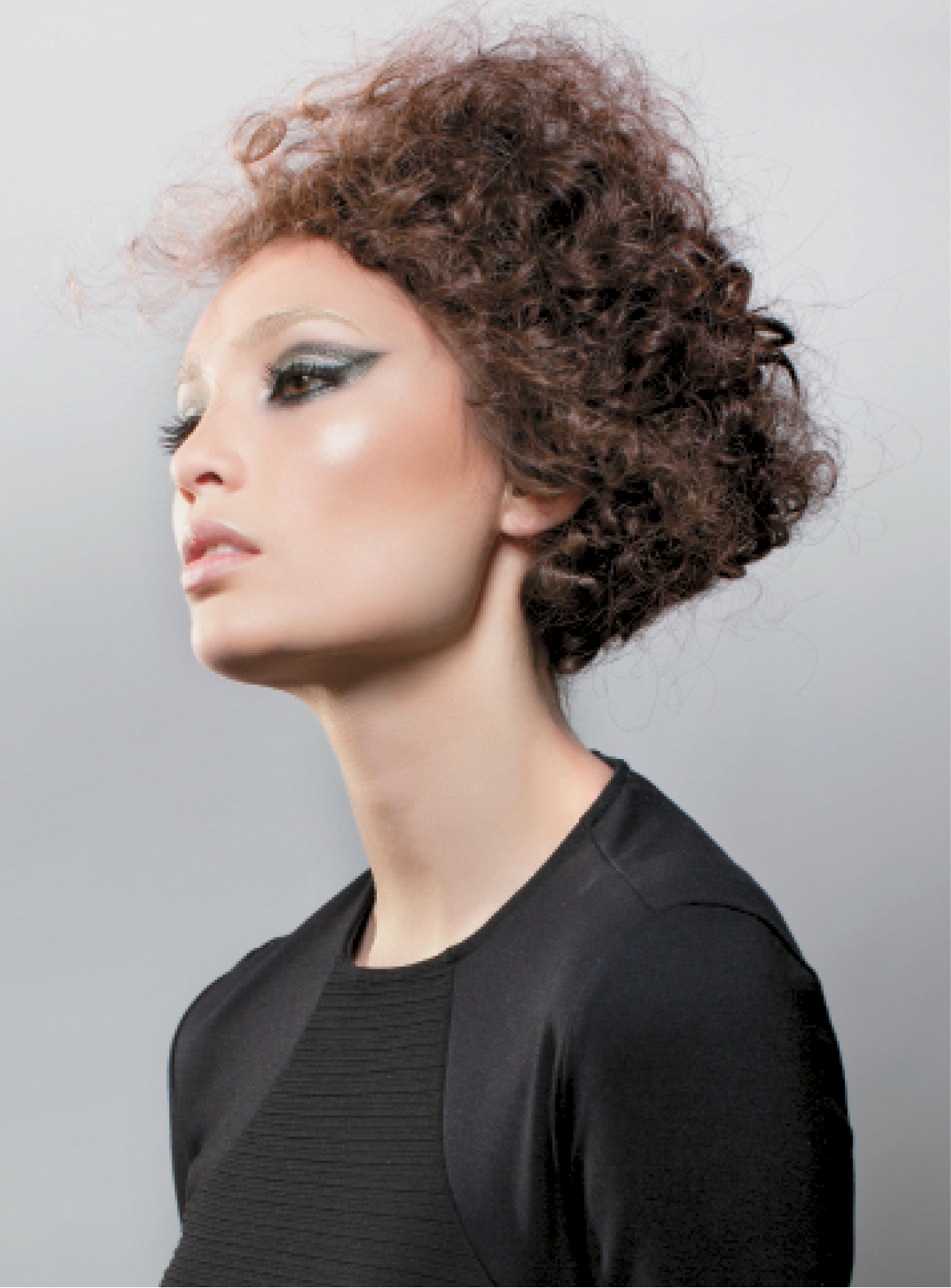 Buccio crafted this geometric square updo by separating every wave and curl without brushing them out. Once he had a full shape, he started to sculpt the hair into a square. He used Osis Session to give the hair hold and pulled out some pieces throughout the perimeter to create a solid shape.