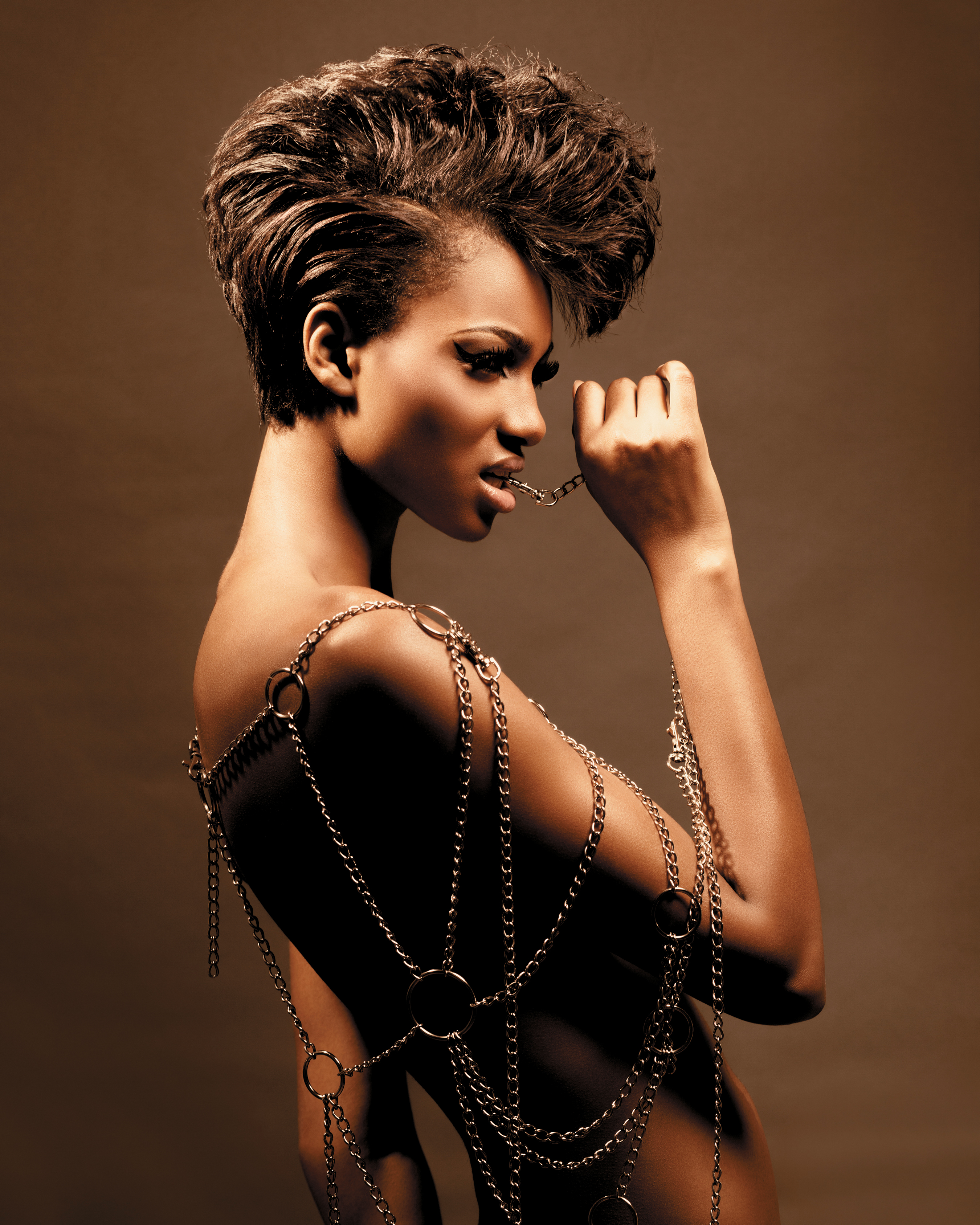 Relaxed hair was styled into a Mohawk. Next, layers were created in the crown area and through the back and sides using a scissor-over-comb technique.
