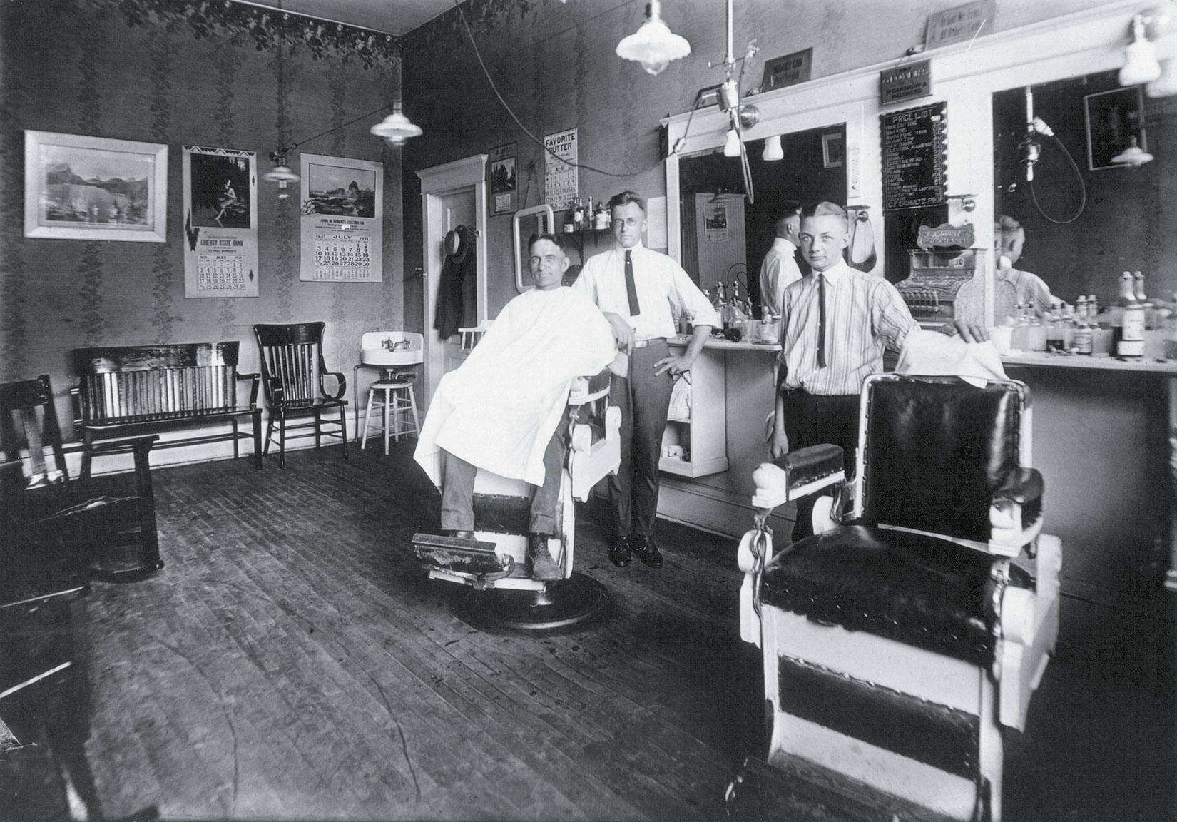 Carl Schulz (far left) with a client in July, 1921. The price list on the wall indicates that a shave was a quarter, a mustache trim a nickel.
