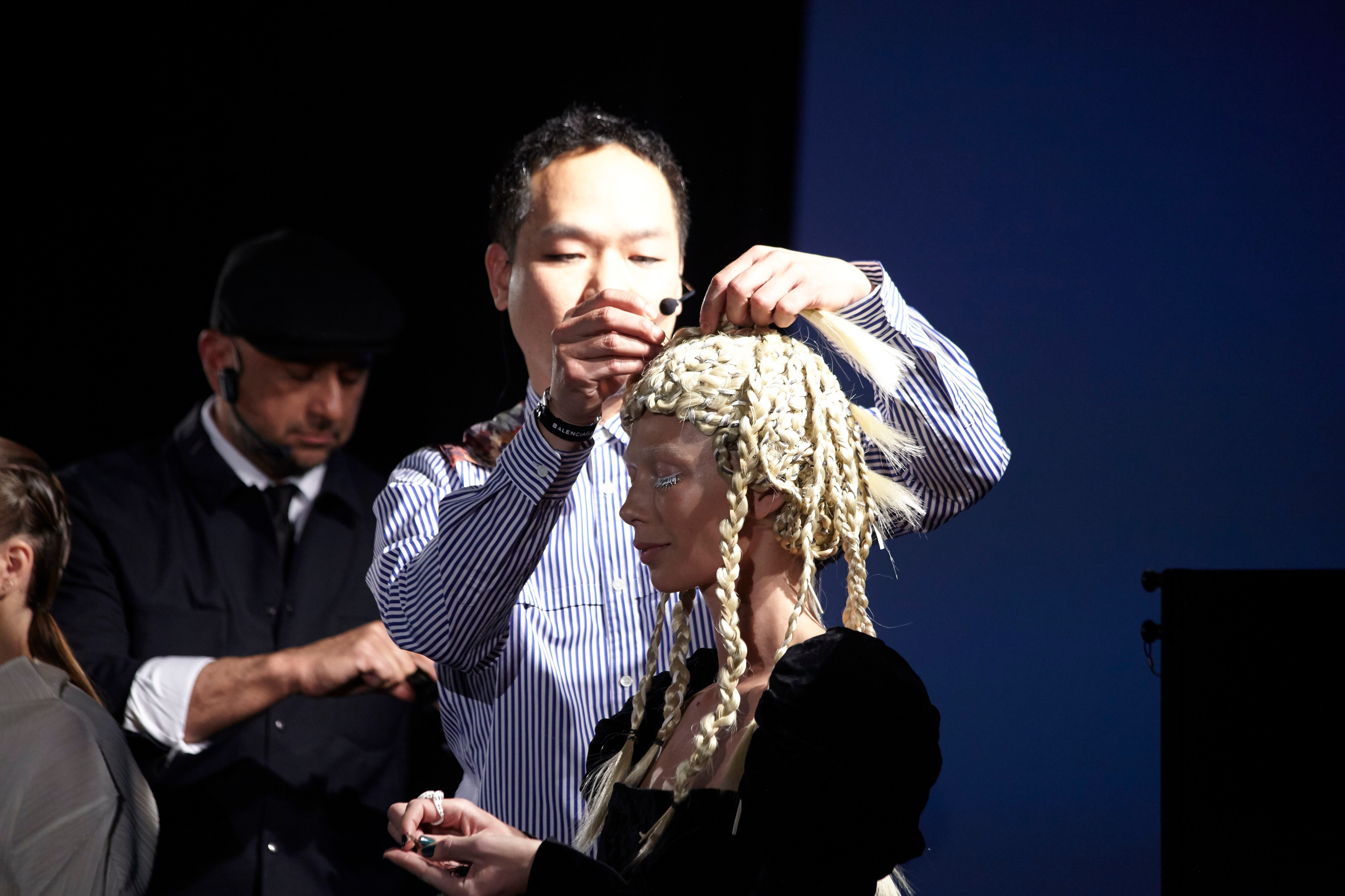 Kien Hoang doing intricate braid work on a model.