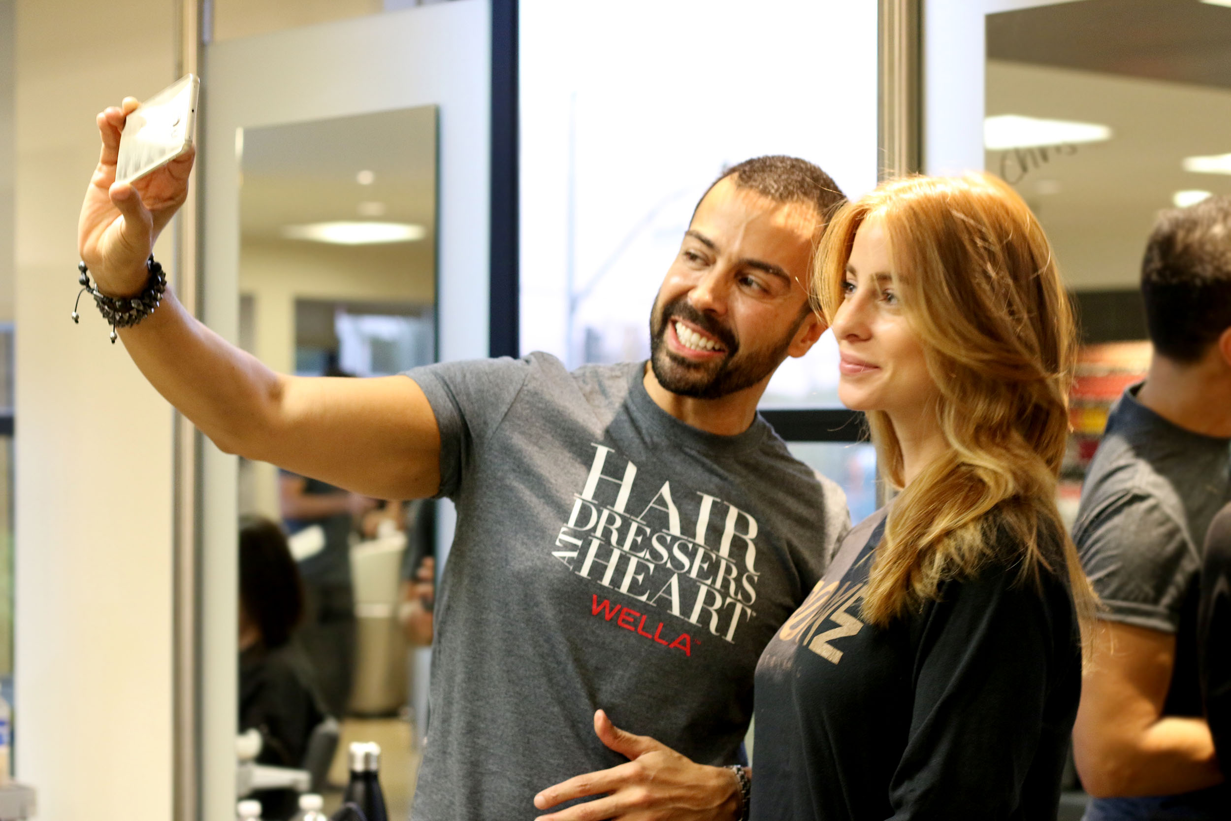Chris Rosario, Sebastian Design artist and Wella Master Color Expert, takes a selfie with a client.