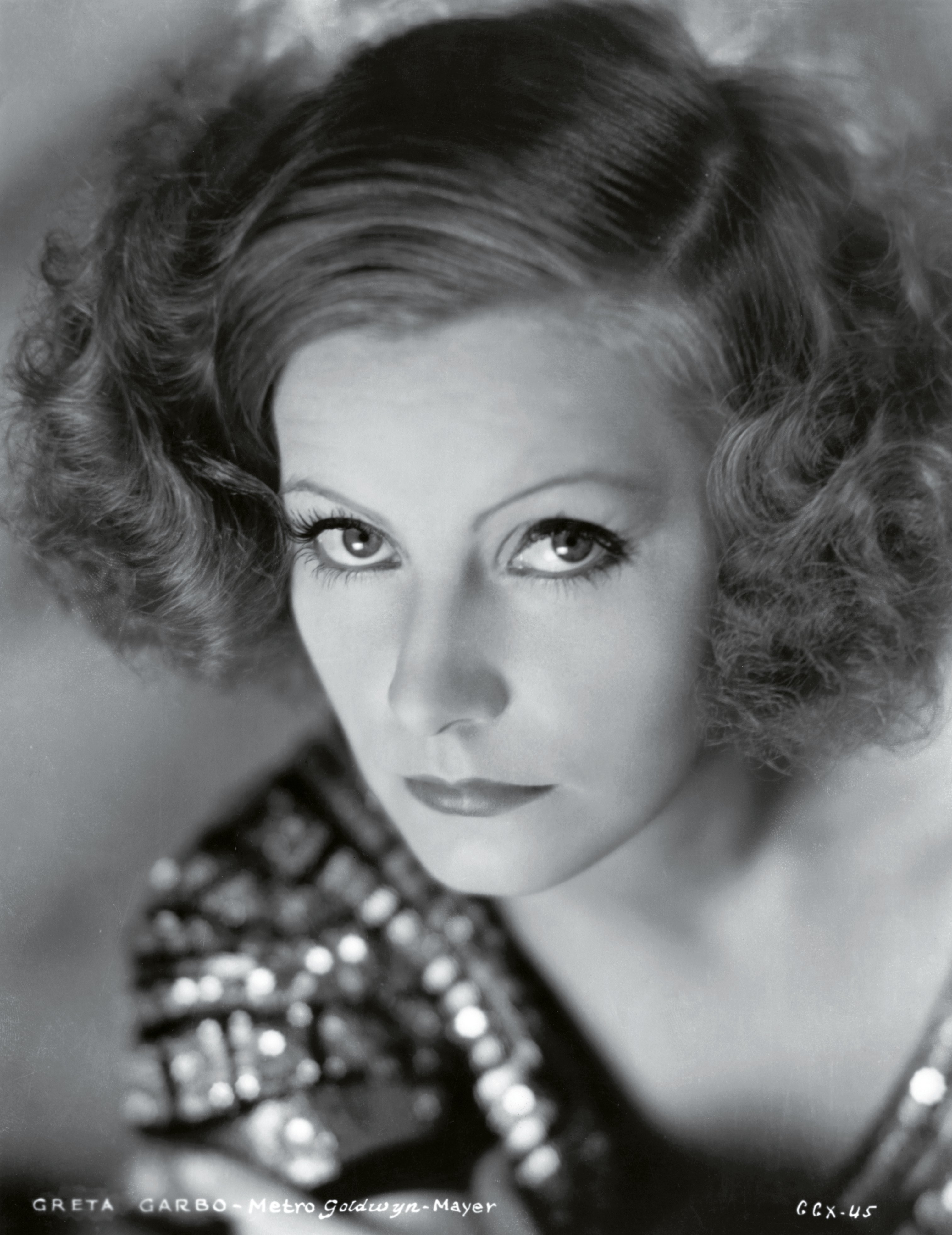 Greta Garbo's shoulder length curly style with a deep side part was another influential style  of the era.