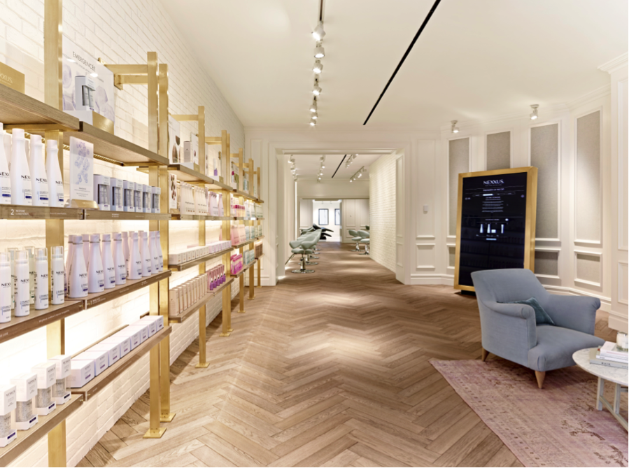 A full product wall on gold shelving opposite the intelligent, interactive mirror.