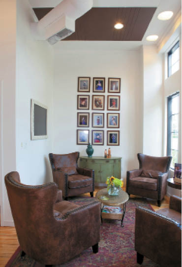 The waiting area at Imprés Salon Spa includes leather chairs and a large area rug for a cozy feel