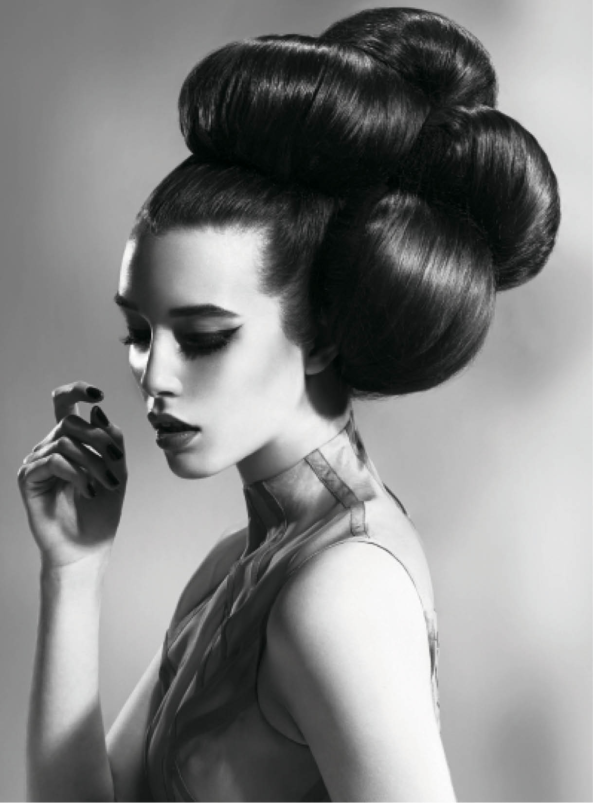 For this voluminous updo, Mather pulled hair into two high ponytails, about one inch apart. She created padding using hair donuts and molded the hair into buns around them.