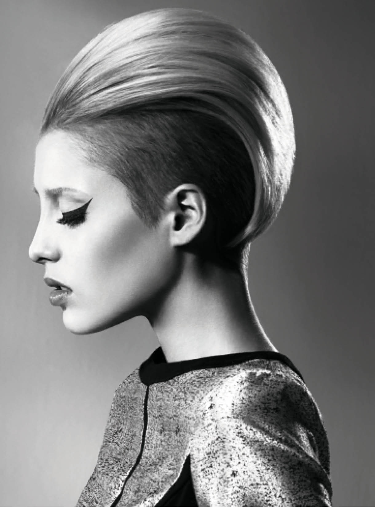 For a contemporary yet retro look, Kerry Mather shaved hair underneath from the ears to the low recession area, maintaining length and weight throughout the top. After drying the hair, she added volume at the crown with crimpers and backcombed, dressing hair over it.