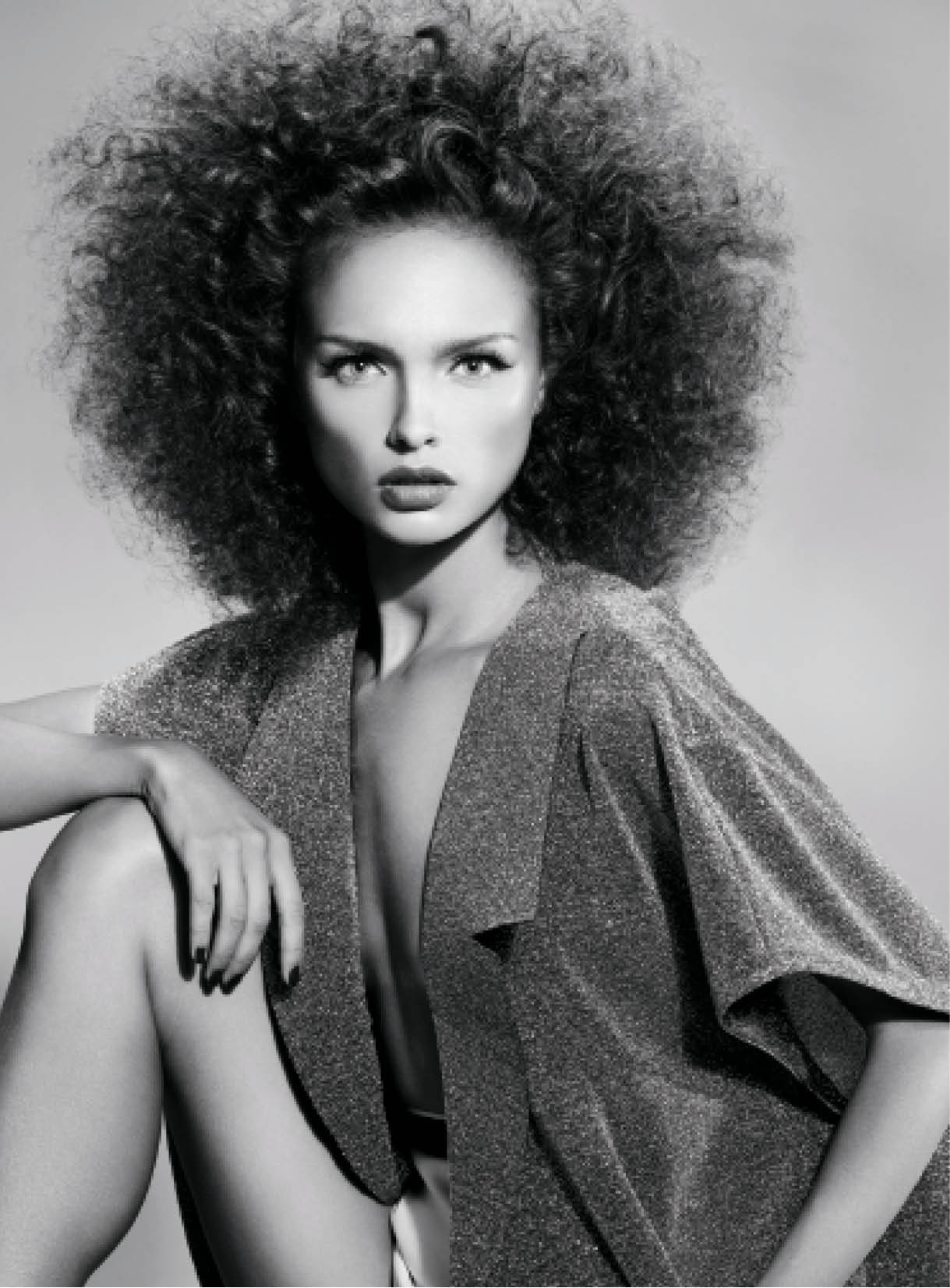 Mather wet-set hair using traditional setting lotion and small perm rollers, allowing two hours for hair to dry. Using a soft bristle brush, an afro comb and her fingers, she created ample volume.