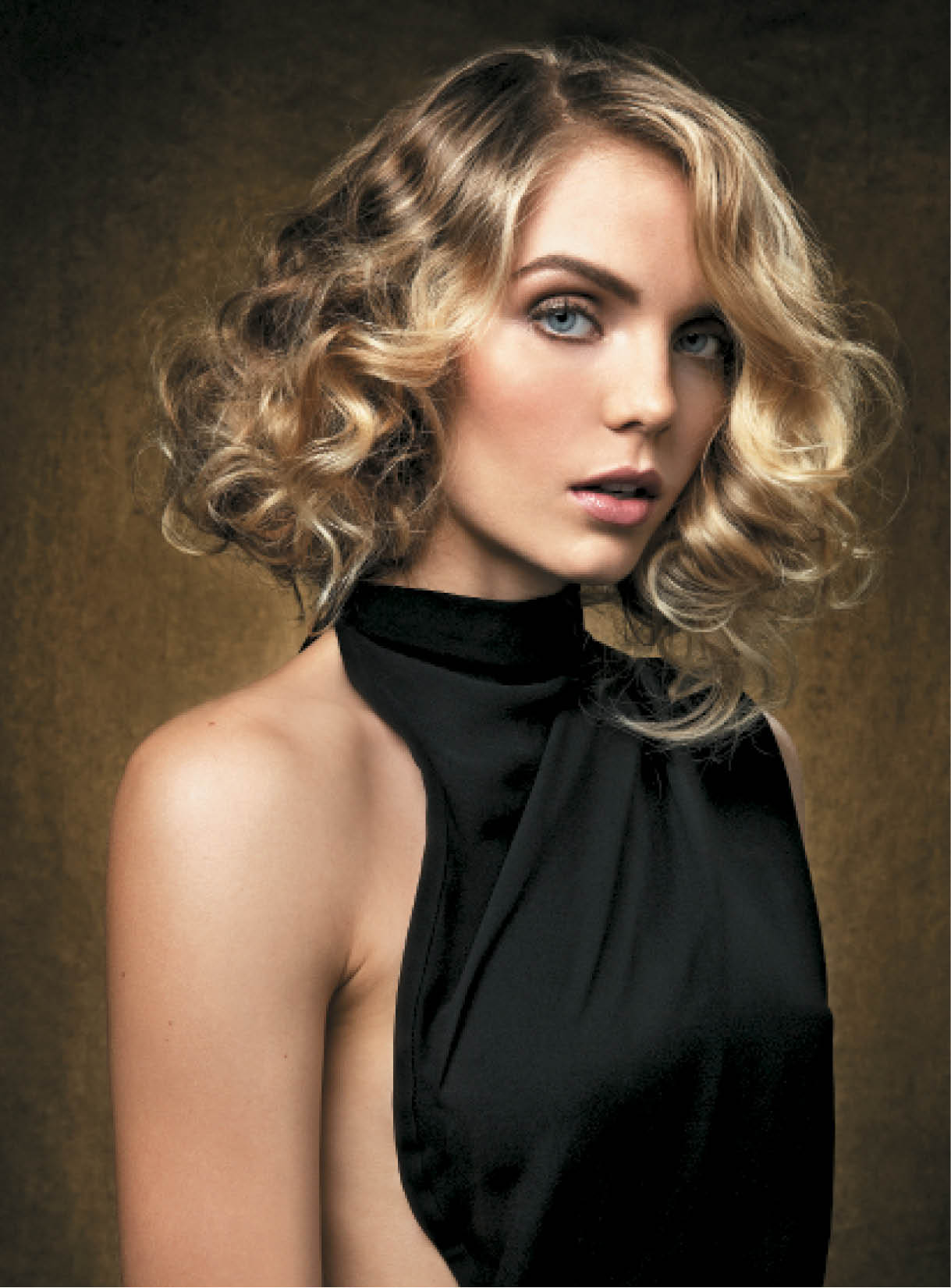 """Amy Poehler's blonde highlight accents at the 2014 Golden Globes inspired this look, which was enhanced by the defined curls in this 'old Hollywood' style,"" Cunningham says."