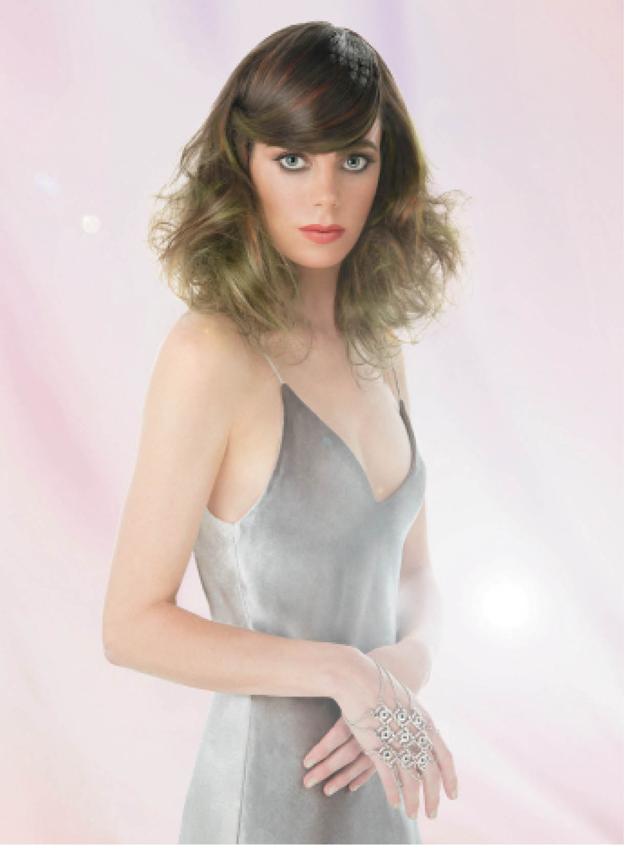 To create this Journey of Enlightenment look, Basham, Lee and Morgan took an offset triangle section in the fringe area, then backbrushed and smoothed it into a sweeping side-shape before pinning it in place. After using a curling iron to create undulating waves, the trio used a brush to smooth the remaining strands around the crown, keeping volume at the ends. For the finishing touch, they used a metal stencil and metallic loose-shadows to embellish the hair.
