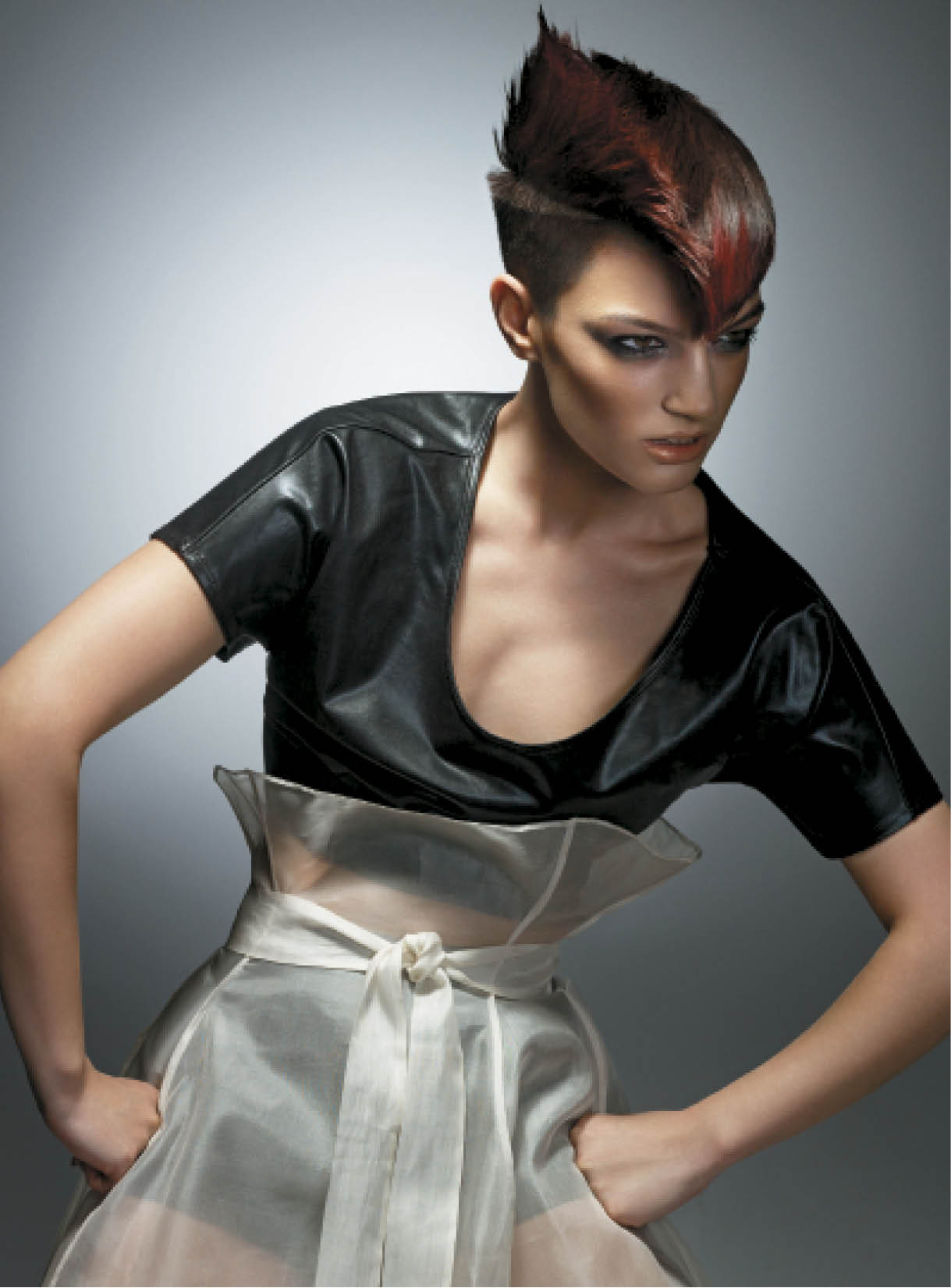 Baek used a scissors-over-comb method, keeping the hair tight to the skin and making sure to keep a strong weight line on the disconnected area. He colored locks an intense red on top and throughout the spiky area and the fringe. For styling, Baek used Tecni.Art Volume Lift, and added Tecni.Art Air Fix and Crystal Gloss while blow-drying to finish the look.