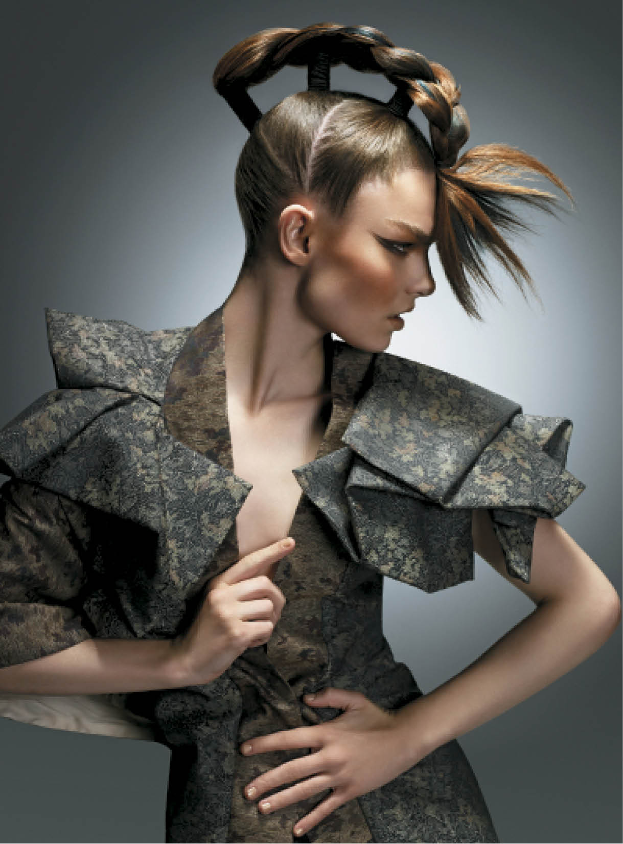 To create a structured style with movement, Baek first sectioned hair into three ponytails and used a plait technique to connect them at the front. Next he tied the hair with elastic and used Deviation Paste to add texture and separation to the hair.