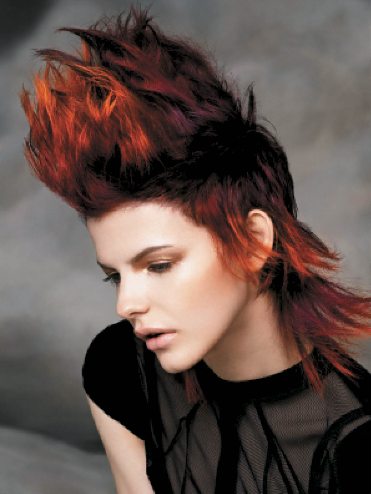 For a red-infused Mohawk, the team ran a flat-iron through the sides and back of the hair. Using a feathering color technique, the team added dark violets, strong coppers and yellows to create depth at the root.