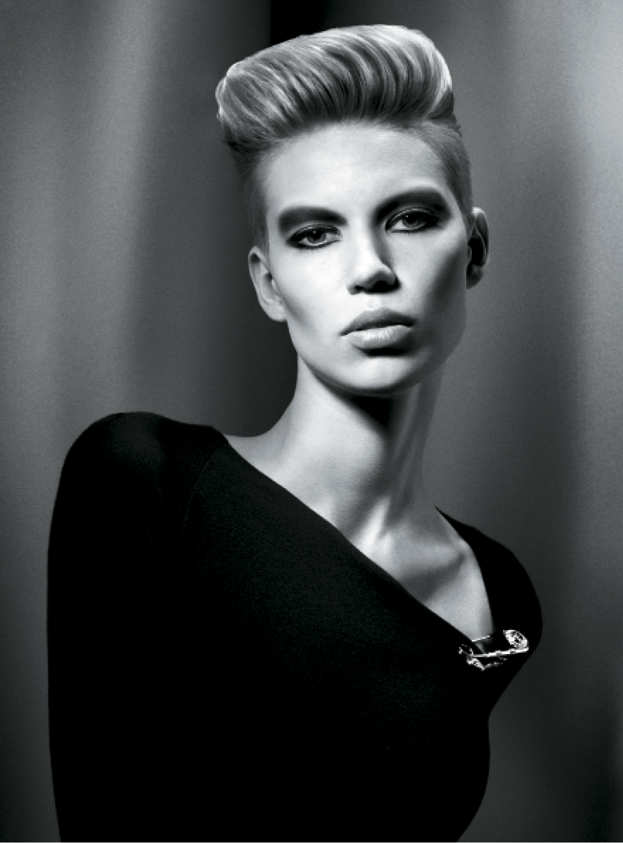To create this take on the pompadour, Mark Leeson applied volumizing mousse to damp hair before blow-drying it with a medium radial brush to create root lift and body. Next, he used a heat protection spray and a large barrel tong to define direction and lift. To finish the look, he spritzed the hair with a light hairspray for touchable hold.