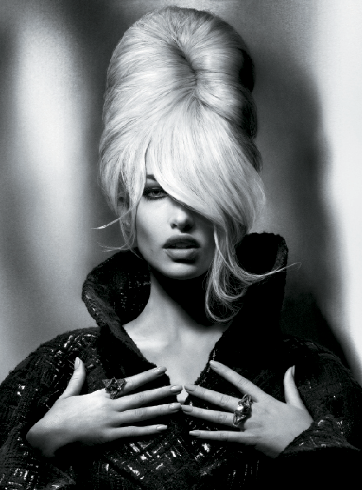 For this sexy shape, Leeson worked volumizing mousse into damp hair, blow-drying it with a large radial brush to amplify shape and movement. Next, he set strands on large heated rollers to enhance bulk and flexibility, then used a backcombing technique in the root area to boost height. Leeson called on a soft bristle brush to smooth layers and give direction to the vertical pleat.