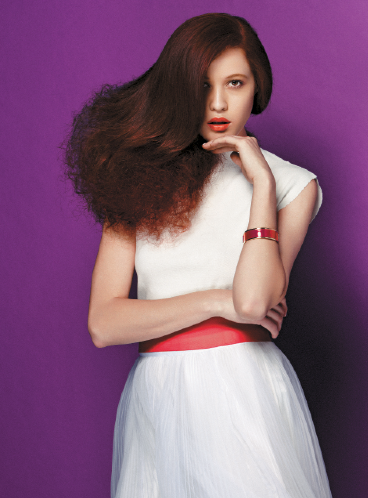 To achieve this tulle-inspired style, Roche prepped hair by blow-drying with Lustrous Volumizer Bodifying Glaze and set it from the nape down by winding hair around a large hairpin, using a figure-eight pattern. She set the top area with a 1-inch iron off base, and then brushed out the underneath section to create the tulle look. After brushing the top section smooth over the tulle, she sprayed hair with Strengthening Control Zero Dulling Hairspray, molding the underneath portion with her hands to create a stronger shape.
