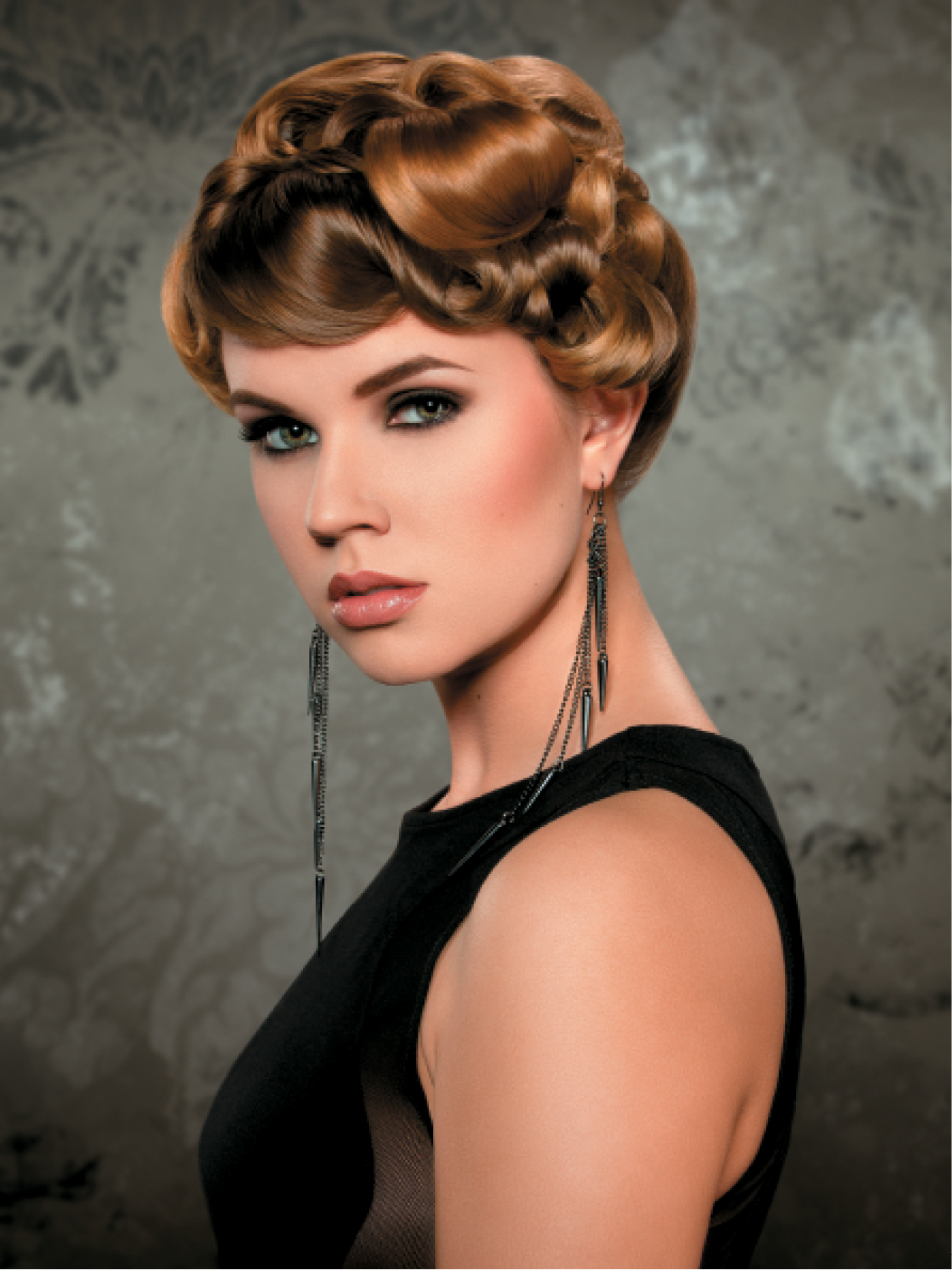 Aurilla Goldsmith set medium-sized hot rollers away from the face in a brick-lay pattern to create a soft bend in the hair. She then parted all sections into different-sized triangles and proceeded with twisting and flat-pinning the hair, with the focal point above the right eye. She polished flyaways with Martin Parsons hairspray.