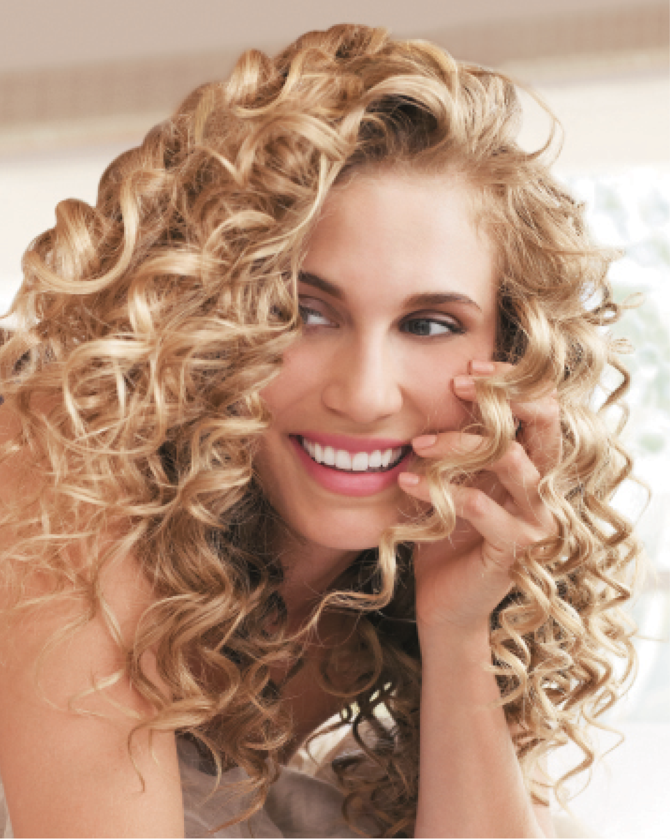 Markham and Wilson prepped natural curls with blonde highlights with TruCurl Curl Perfecting Shampoo and Condition before mixing TruCurl Curl Perfecting Crème and TruCurl Anti-Frizz Oil and applying it to damp hair. After diffusing hair until completely dry, they wrapped 1-inch hair sections around closed-barrel curling irons, alternating between small and very small sizes in clockwise and counterclockwise directions.