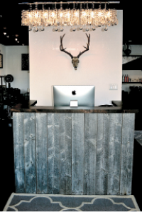 Antler wall decor and a chandelier at the front desk support a Western-meets-elegant theme