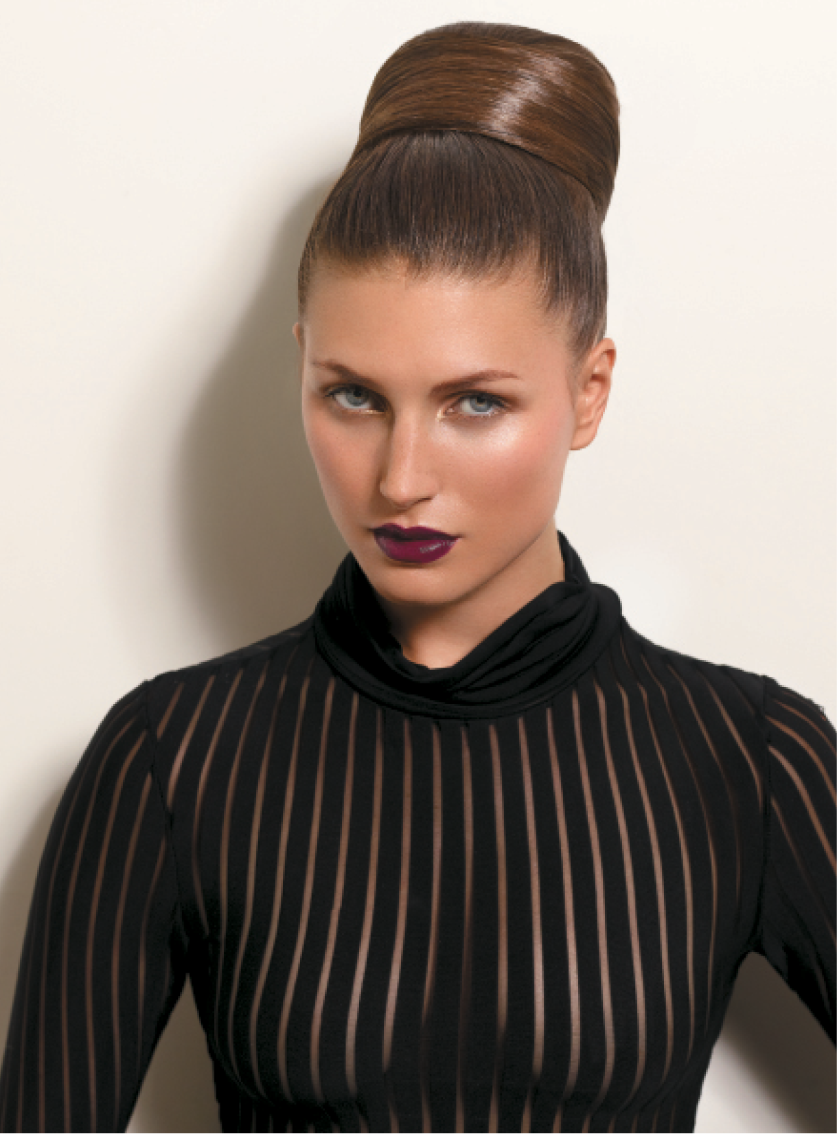 To create this majestic top knot, Lucie Doughty pulled the hair into a high ponytail that she affixed with two bobby pins and a hairband. After securing additional padding with pins from her Straight Pin Studio Big Bun Trend Kit, Doughty folded the hair over the padding before wrapping it around to form a large bun. A spritz of Paul Mitchell Awapuhi Wild Ginger Shine Spray completed the look.