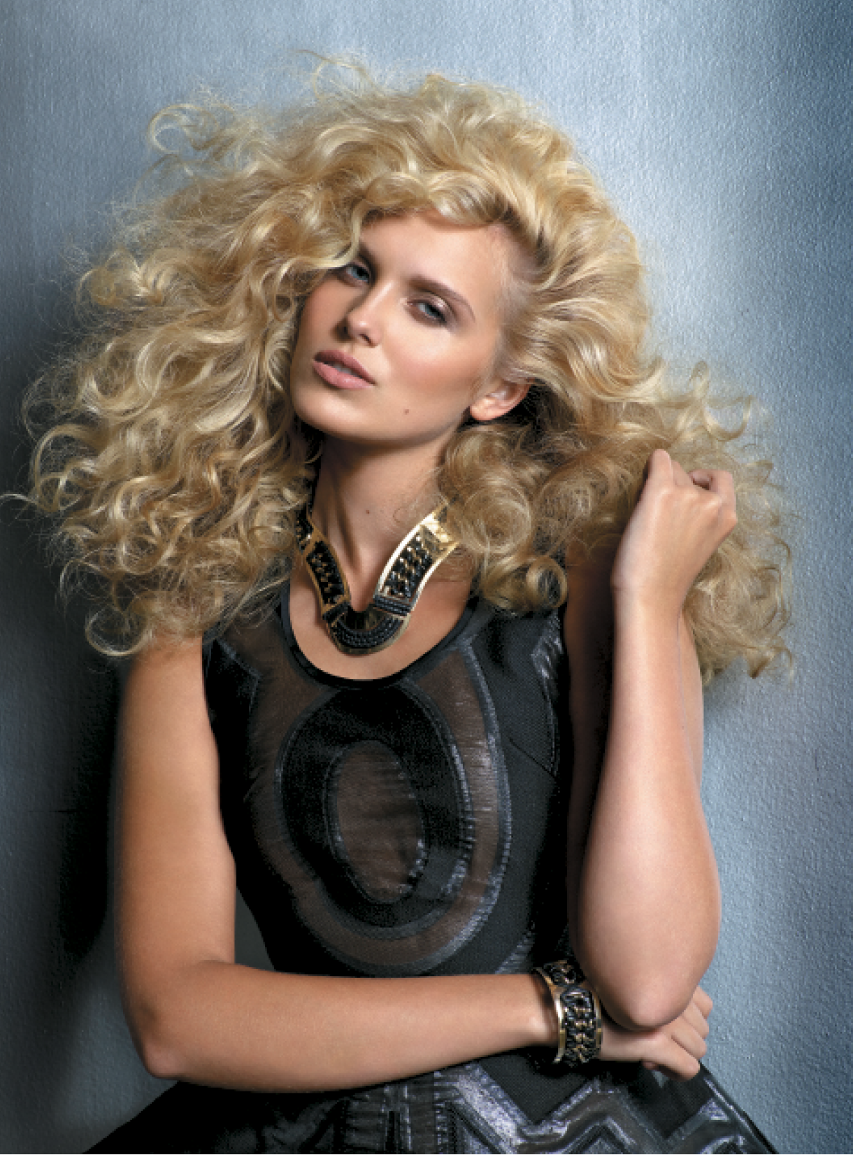 After applying Foaming Volumizer all over and rough-drying hair upside down, Giannandrea used a ½-inch curling iron and Control Hairspray to set small sections. Once they cooled, he used a wide-tooth comb and Activating Curl Cream to amplify volume and create bouncy waves and curls. Jewelry: Pluma; Dress: Cristiano Burani