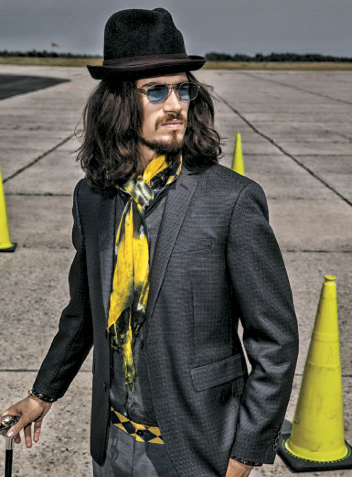 To amplify texture, Brunetti worked a light pomade into the hair, then used a diffuser to slowly dry it and enhance the natural wave pattern. Suit and top: Moschino; scarf:  Etro; belt: H.E. by Mango; glasses: Vintage Matsuda; cane: Asprey; hat: Bar III